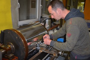 A pipemaker working with the metal plane.